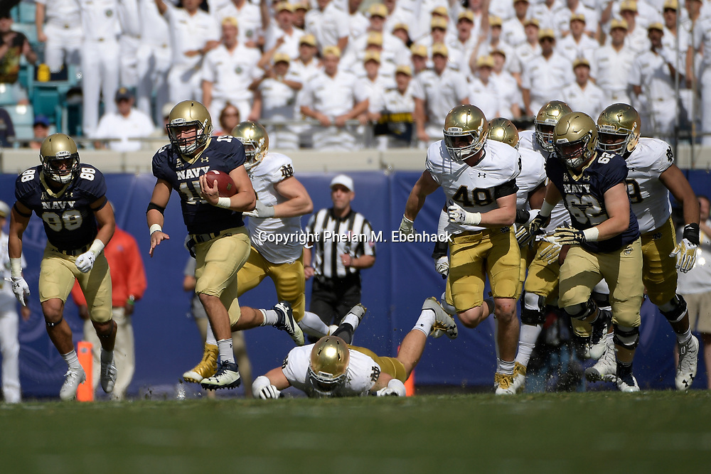 Navy quarterback Will Worth (15) rushes for a long gain past Notre Dame linebacker Greer Martini (48) during the first half of an NCAA college football game in Jacksonville, Fla., Saturday, Nov. 5, 2016. (Photo by Phelan M. Ebenhack)