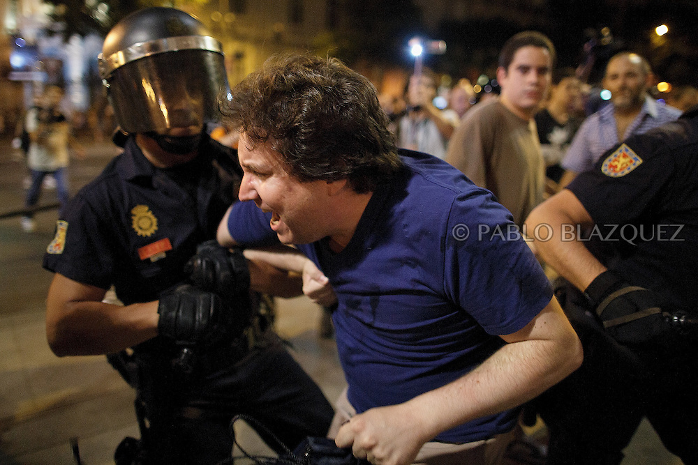 Riot police detain a protestor after clashes in Cibeles Square during a demonstration against the Spanish government, on Thursday, July 18, 2013, in Madrid, Spain. Thousands demonstrators demanding the resignation of Prime Minister Mariano Rajoy and its party gathered in front of the People's Party headquarter. Rajoy rejected demands to resign after more alleged secret payments and test messages related to former political party treasurer Luis Barcenas under investigation appeared. The spectacle of alleged greed and corruption has enraged Spaniards hurting from austerity and sky high unemployment.