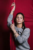 """NAPLES, ITALY - 16 MARCH 2018: Angela Cuccaro (19), an aerial dancer, poses for a portrait at """"Il Tappeto di Iqbal"""" (Iqbal's carpet), a non-profit cooperative in Barra, the estern district of Naples, Italy, on March 16th 2018.<br /> <br /> Il Tappeto di Iqbal (Iqbal's Carpet) is a non-profit cooperative founded in 2015 and Save The Children partner since 2015 that operates in the Naple's eastern neighborhood of Barra children in the arts of circus, theater and parkour. It was named after Iqbal Masih, a Pakistani boy who escaped from life as a child slave and became an activist against bonded labor in the 1990s.<br /> Barra, which is home to some 45,000 people, has the highest rate of school dropouts in the Italian region of Campania. Once a thriving industrial community, many of the factories were destroyed in a 1980 earthquake and never rebuilt. The resulting de-industrialization turned Barra into a poor, decaying neighborhood. There are no cinemas, theaters, parks or public spaces in Barra.<br /> The vast majority of children from poor families are faced with the choice of working in the black economy or joining the ranks of the organised crime.<br /> Recently, Save the Children Italy opened a number of educational and social spaces in Barra. The centers, known as Punti Luce, or points of light, aim to help local kids stay out of the ranks of the organised crime and have also become hubs for Iqbal's Carpet to work."""