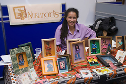 Young artist standing by her stand at Nottingham's 'Women's Enterprise Day' exhibition; held at the New Deal for Communities centre,