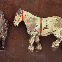 Close up of battered and scratched lead models of plump old farmer and white carthorse lying on rusty metal sheet