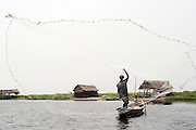 Benin March 1, 2008 Beninese fisherman work from his pirogues at dawn on the lagoon of Ganvie