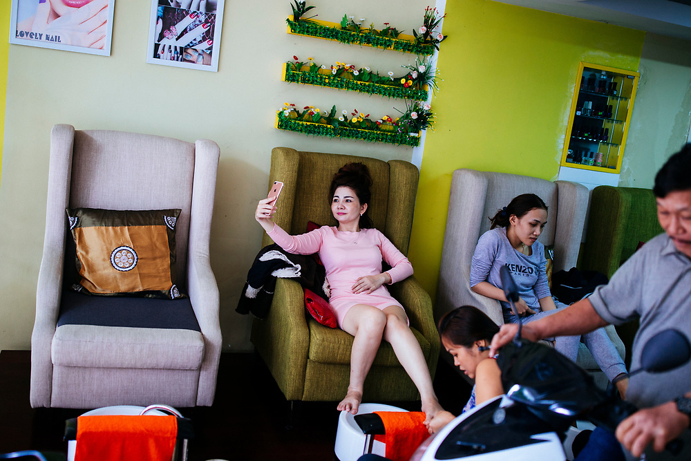 A woman takes selfies while getting her nails done in Danang, Vietnam.