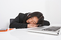Exhausted businesswoman resting at office desk
