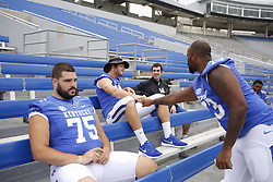 Kentucky offensive tackle Kyle Meadows pounds Kentucky quarterback Patrick Towles on the way to sit down in the stands during the University of Kentucky's annual media day, Friday, Aug. 07, 2015 at Commonwealth Stadium in Lexington.