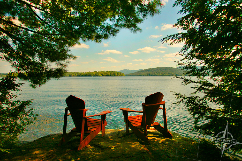 Adirondack Chairs by a Lake in summer.