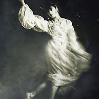 A monochromatic image of a woman in a white gown and a decorative headdress, in a dancing pose and tense expression.