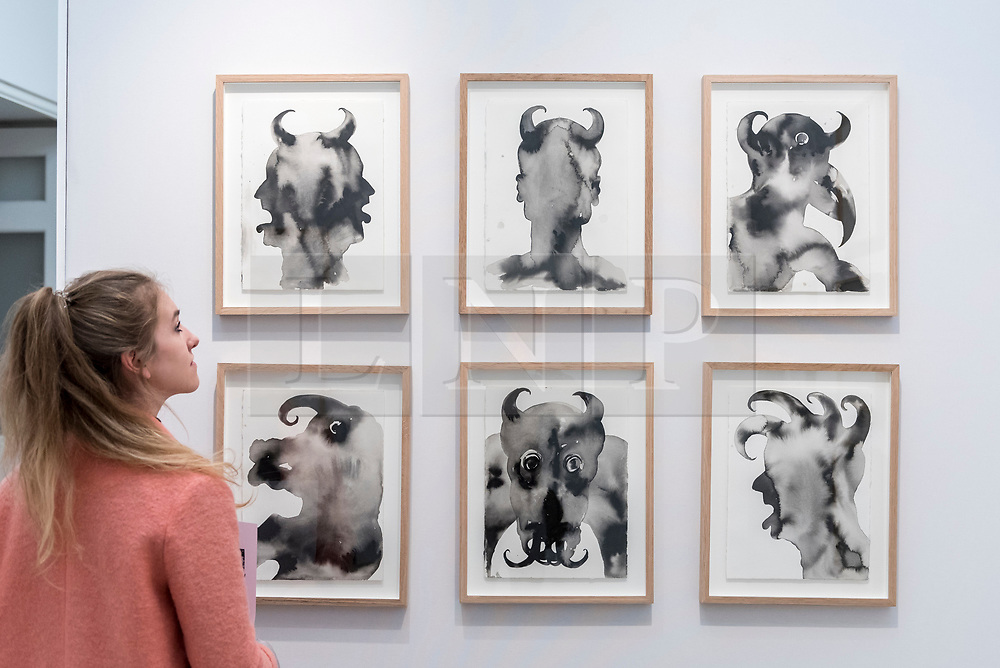 """© Licensed to London News Pictures. 17/05/2019. LONDON, UK. A visitor views a series of works called """"Devil Heads"""", 2009, by Barthélémy Toguo at the HdM Gallery during the Draw Art Fair London, the first fair in the UK dedicated to modern and contemporary drawing.  58 international galleries have juxtaposed drawings with related paintings, sculptures, photos or videos, in a ratio of approximately 70% to 30%, using drawing as the core concept.  The inaugural show is open to the public 17 to 19 May 2019 at the Saatchi Gallery in Chelsea.  Photo credit: Stephen Chung/LNP"""
