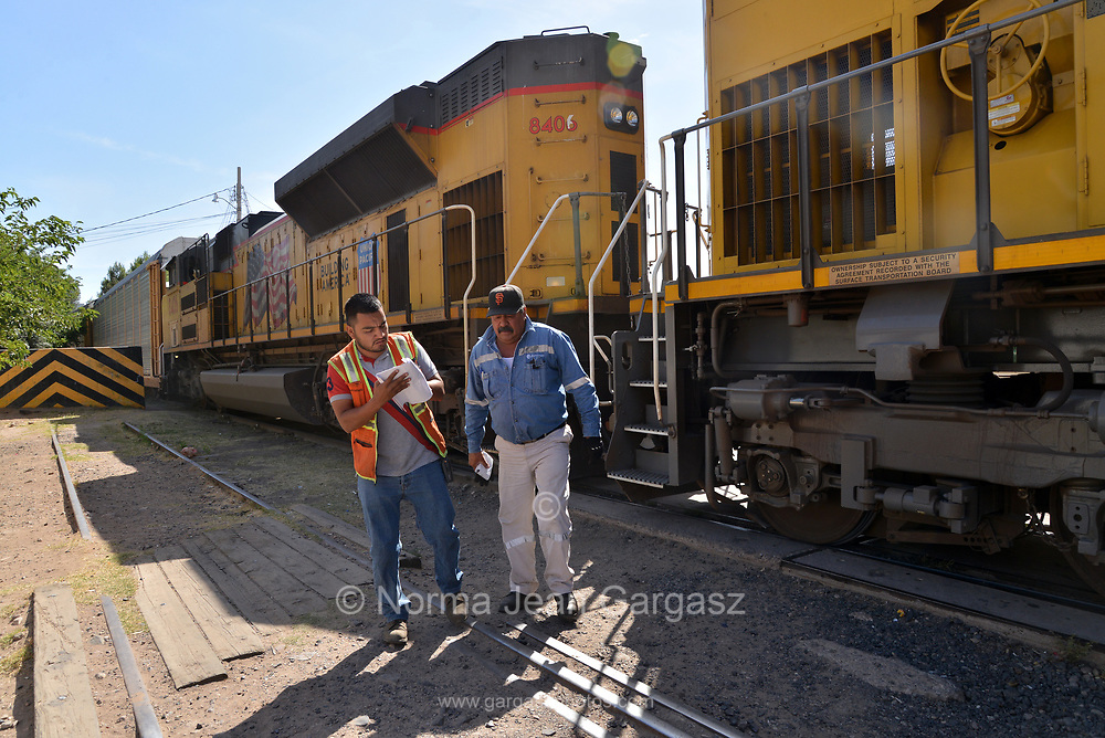 A train hauling mostly manufactured automobiles stops in Nogales, Sonora, Mexico, to be processed before entering a metal gate at the Dennis DeConcini Port of Entry to enter the United States at Nogales, Arizona.  Personnel with Ferromex, the company operating the train in Mexico, depart the train before it enters the U.S.