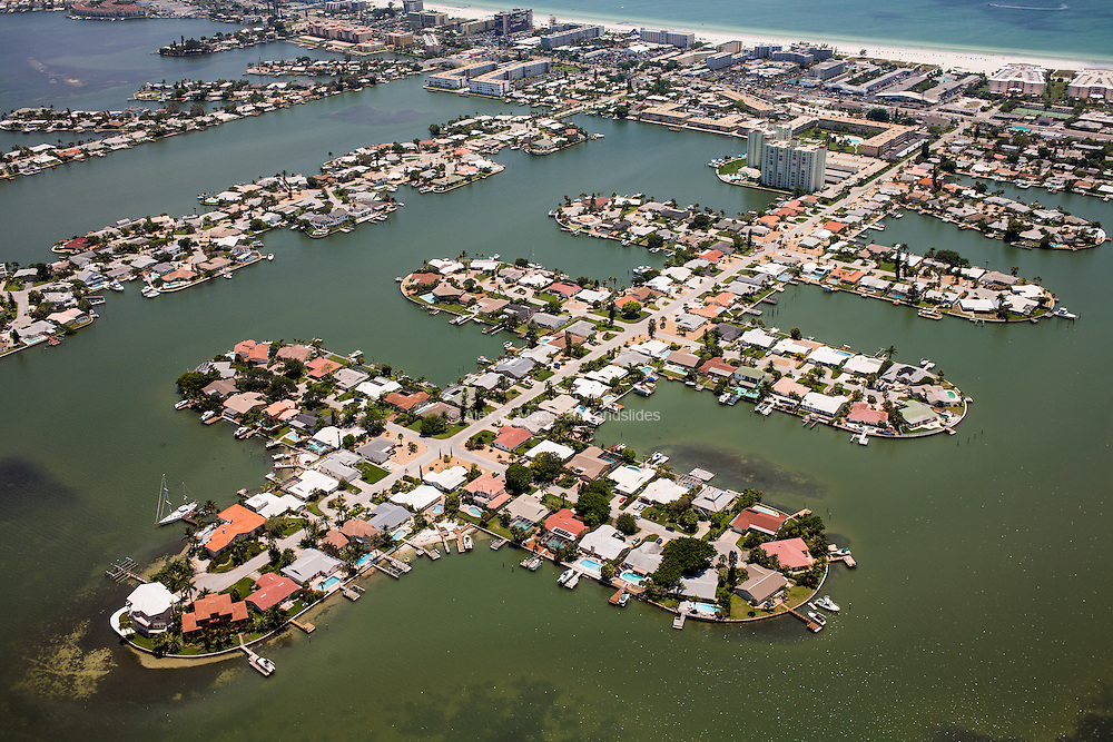 The construction of artificial dredge-and-fill peninsulas for housing behind barrier islands on the Gulf Coast is a common technique for creating waterfront property along much of the Florida coastline, all of which is vulnerable to flooding and storm surges.