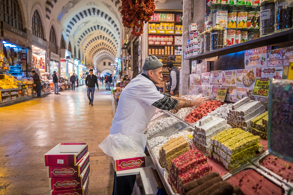 Male merchant organizing the display of Turkish delights at this market stall in Istanbul Spice bazaar in Turkey