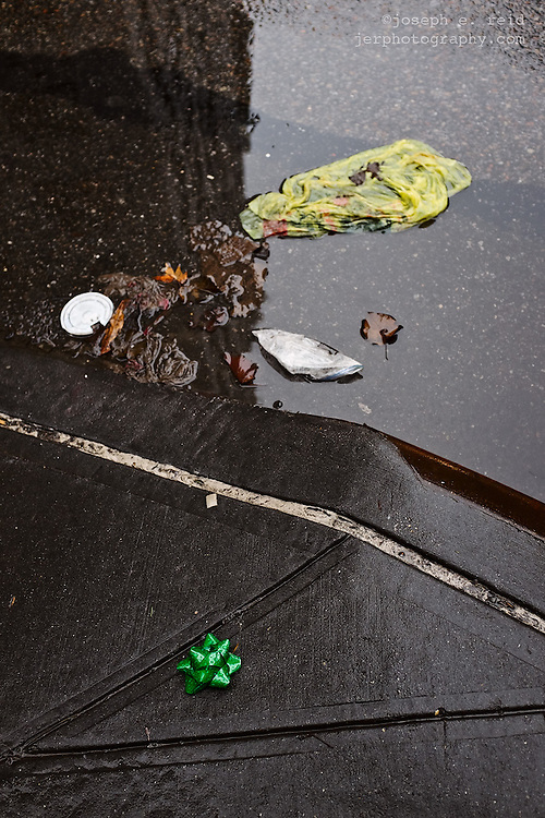 Christmas bow and litter on wet street, New York, NY, US