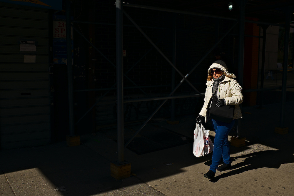 Woman in white coat with large white shopping bag, New York, NY, US