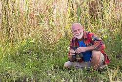 mature man squatting down with binoculars outdoors in The Everglades