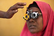 "Dadaab, Kenya -   2014-08-15 - Maryan Ali Olow has her eyesight examined by Ophthalmic Clinical Officer Winston Anzere at the IRC eye centre (Integrated Primary Eye Care Programme, Dadaab Refugee Camp/Kenya, P2778) in Hagadera Camp, Dadaab, Kenya on August 15, 2014. ""In under five minutes we found the problem, all she needs is spectacles,"" Anzere says.  Photo by Daniel Hayduk"