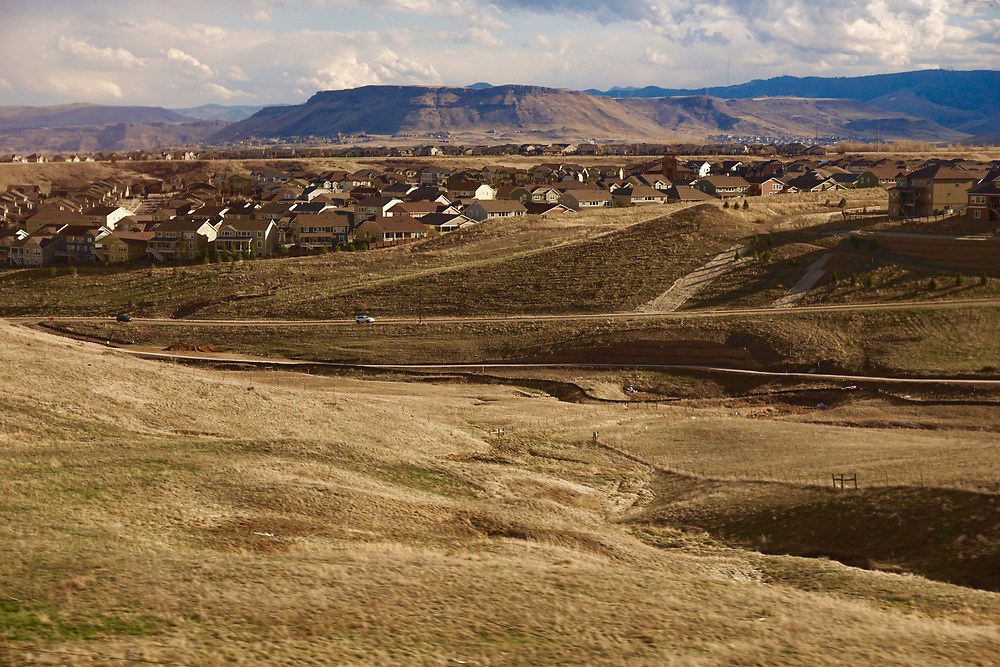 Amtrak Zephyr landscape view with grassland and village west of Denver on Train line.