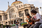 Mexican teens play guitar in Alameda Central park outside the Palacio de Bellas Artes in Mexico City, Mexico.
