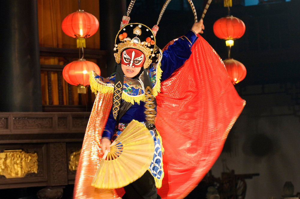 Traditional mask-changing costumed dancer performs on stage of the Theatre of Wu Hou Shrine in Chengdu, Sichuan Province, China