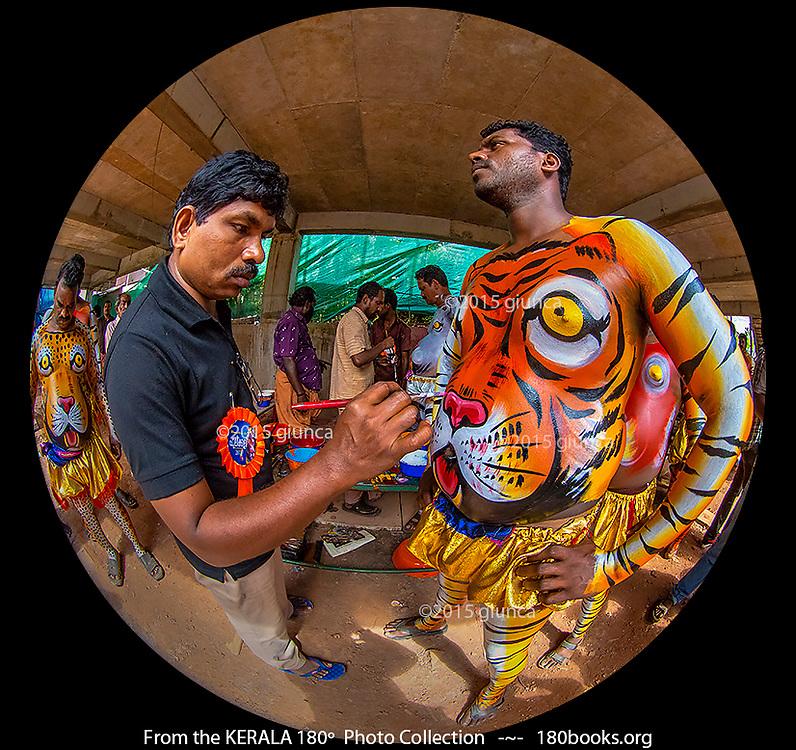 A make-up artist applies the finishing touches to a Kaduvakali dancer