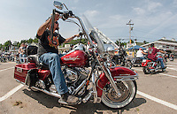 A steady stream of motorcyclists parade down Lakeside Avenue on Tuesday during Laconia's 91st Motorcycle Rally.   (Karen Bobotas/for the Laconia Daily Sun)