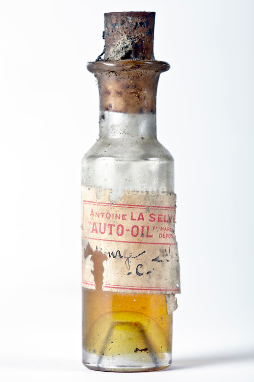 old little bottle with yellow liquid mentioning on the label auto oil