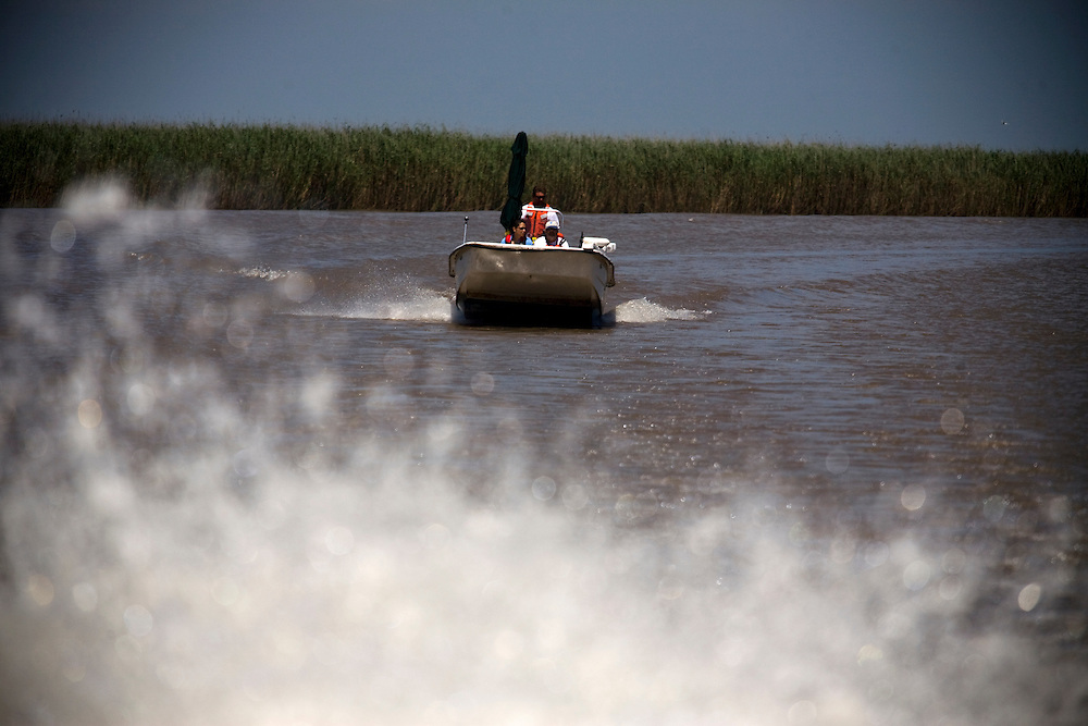 From left, Stacy Villanueva  of Entrix (a company contracted by British Petroleum), Capt. Paul Whipple, and Howard Schnabolk of the National Oceanographic and Atmospheric Association (NOAA) head out through the South East Pass in southern Louisiana to conduct experiments near Venice, LA on June 25, 2010. The group is building evidence to assess the amount of damages done by the Deep Horizon British Petroleum oil spill which has been called the largest man-made natural disaster in American history. (Dominic Bracco II for The Wall Street Journal)
