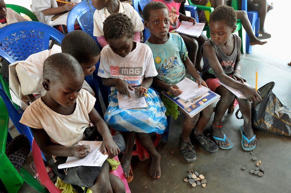 Children learning math at an outdoor class at the Lumege-Canjamba primary school. The area around the school was contaminated with landmines during Angola's long civil war, preventing many children from coming to school and limiting the movement of those who did. Mines Advisory Group (MAG) cleared the area of mines and other remnants of war allowing children to receive an education safely and for plans to build more class rooms to accomodate an increasing number of students who are arriving under the government's Village Reunification Program - a program that encourages families living in remote hamlets to move to larger villages so that the government can provide basic services such as education, health care, water and electricity. .Lumege Canjamba, Angola. 30/09/2010.Photo © J.B. Russell