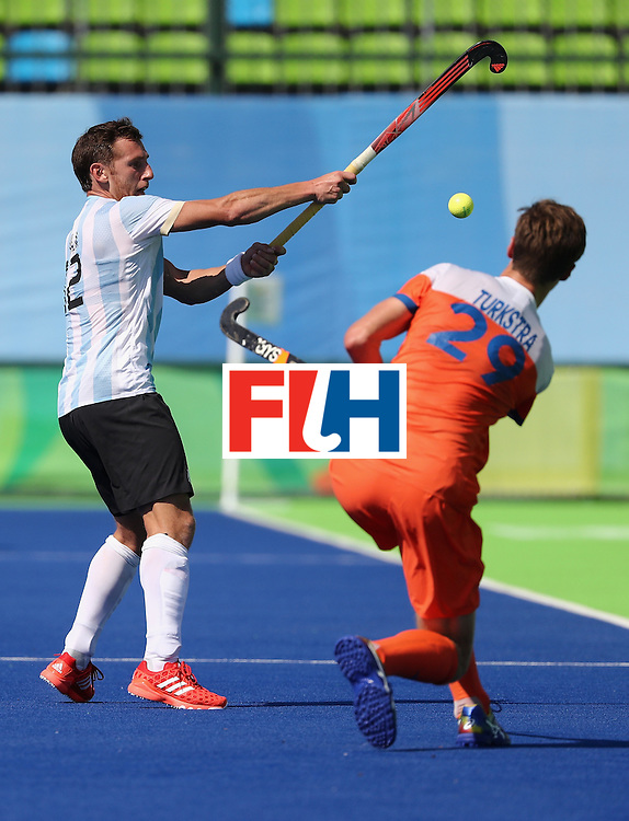 RIO DE JANEIRO, BRAZIL - AUGUST 06:  Lucas Vila #12 of Argentina competes against Hidde Turkstra #29 of Netherlands during a Pool B match between Argentina and Netherlands at Olympic Hockey Centre on August 6, 2016 in Rio de Janeiro, Brazil.  (Photo by Sean M. Haffey/Getty Images)