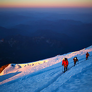 Climbers ascend Mount Rainier at sunrise as Mount Adams can be seen in the background on June 30, 2015. The iconic Pacific Northwest volcano is a popular challenge for mountaineers.  (Joshua Trujillo, seattlepi.com)