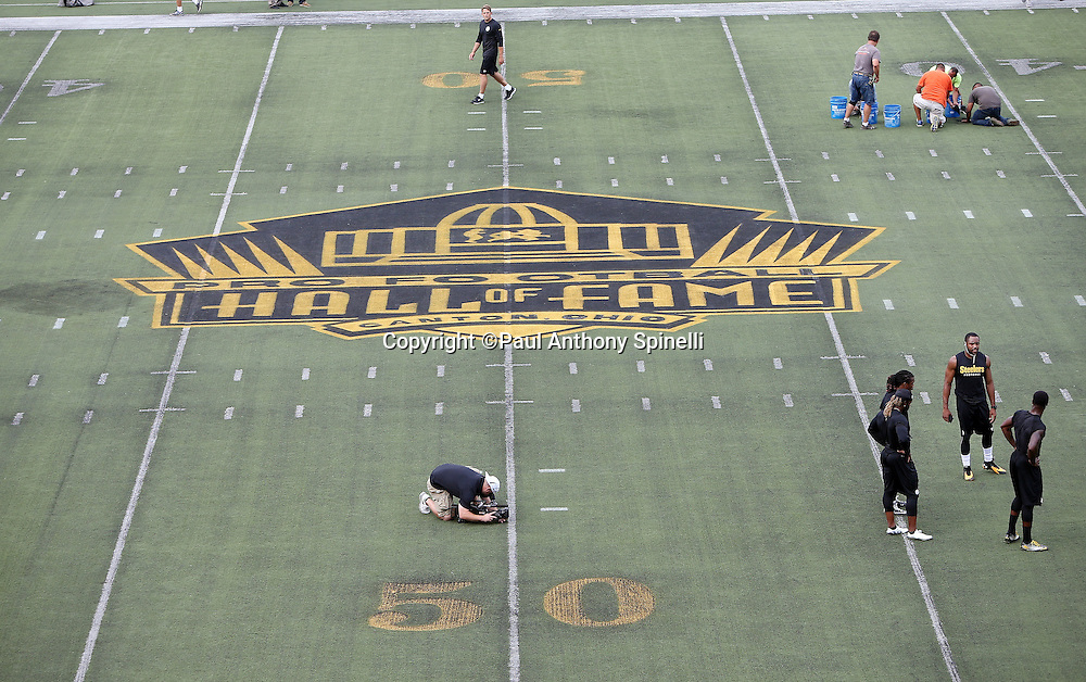 The Pro Football Hall of Fame logo is painted on the field at Tom Benson Hall of Fame Stadium as Pittsburgh Steelers players warm up before the 2015 NFL Pro Football Hall of Fame preseason football game against the Minnesota Vikings on Sunday, Aug. 9, 2015 in Canton, Ohio. The Vikings won the game 14-3. (©Paul Anthony Spinelli)