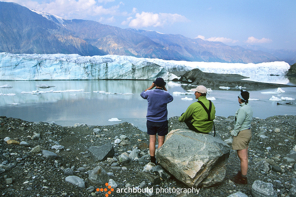 Three hikers look out at the Donjek Glacier in Yukon, Canada