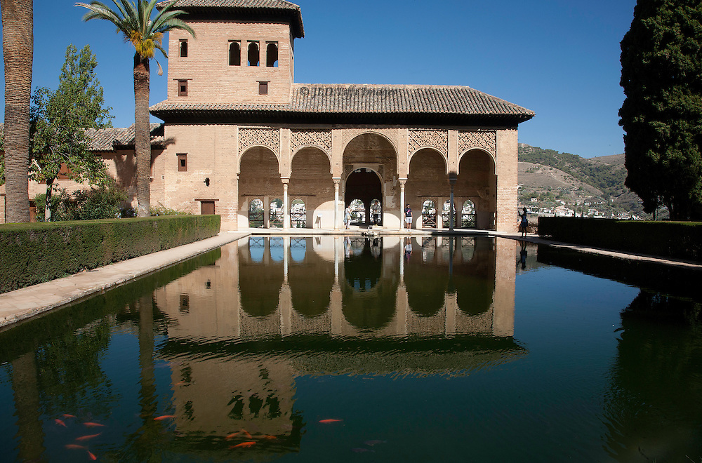 Facade of the Generalife palace at the Alhambra, Granada, reflected in the pool in the foreground.  Four tourist figures at in the distance, goldfish swimming in the foreground.