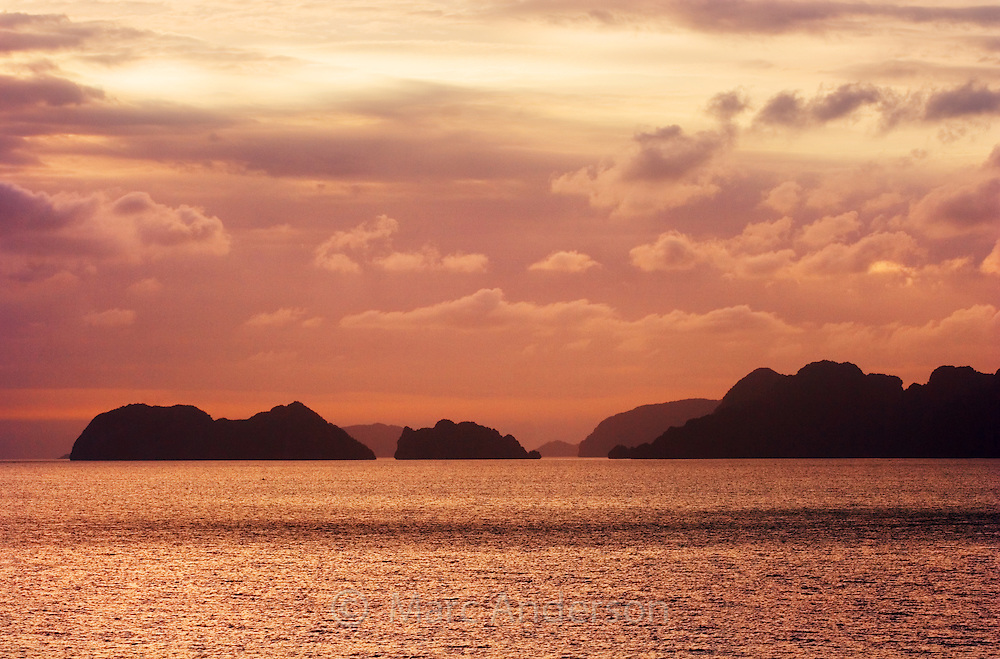 Sunset silhouette of jagged limestone islands in the Bacuit Archipelago rising from the horizon, El Nido, Palawan, Philippines..