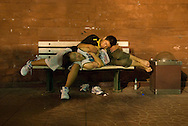 A teen age couple sleeping on a bench. During summer nights, on Changan jie, near Tian An Men square, the benches are occupied by tourists, homeless, migrant-workers who spend the night there waiting for the sun to rise.