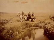 Three Piegan men on horseback in open grassland near pond, c1900.  Photograph by Edward Curtis (1868-1952).