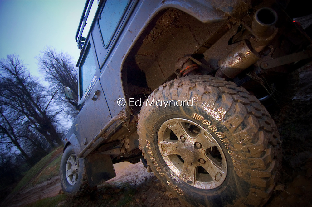 Close up of the rear tyre of a Land Rover Defender 90 traversing muddy ground and demonstrating extreme axle articulation, England, United Kingdom.