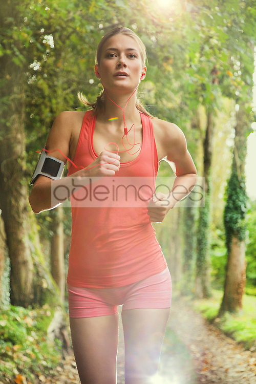 Woman Running in Tree Lined Path