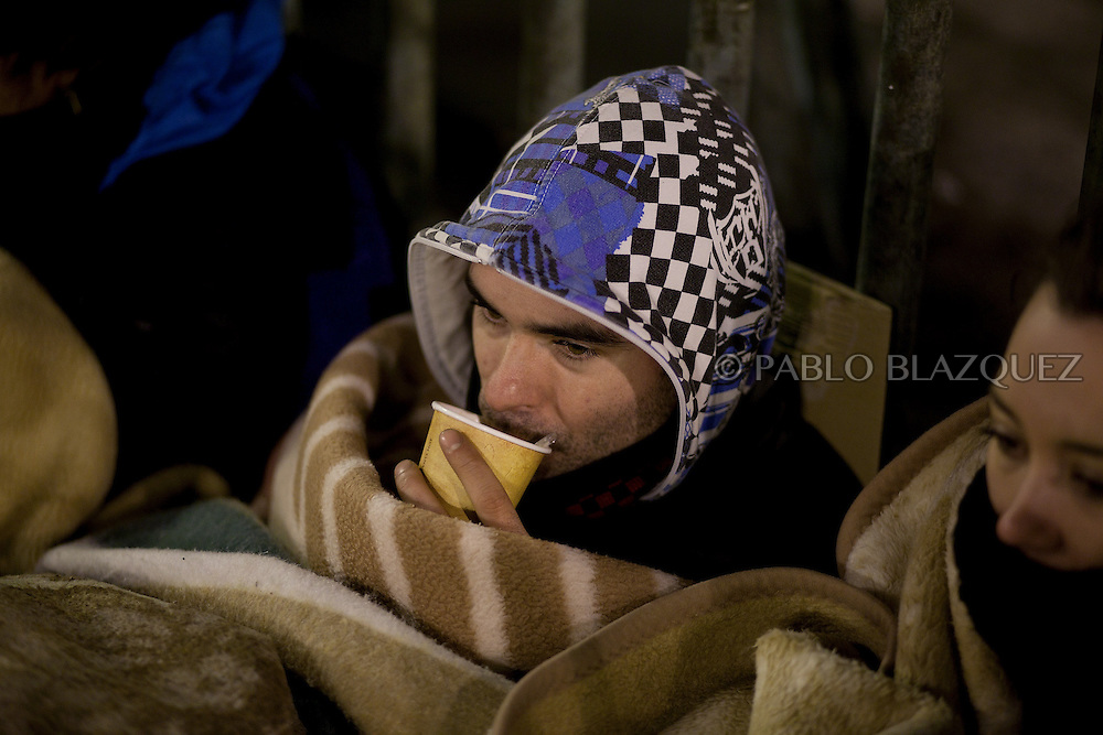 A demonstrator has a coffee on the first night of a camp protest in Puerta del Sol Square after a demonstration against alleged corruption scandals implicating the PP (Popular Party) on February 4, 2013 in Madrid, Spain. Spain's Prime Minister Mariano Rajoy yesterday denied receiving undeclared payments from his political party. More information on secret payments were revealed today and leader of opposition socialist Party (PSOE) urged Rajoy to resign.