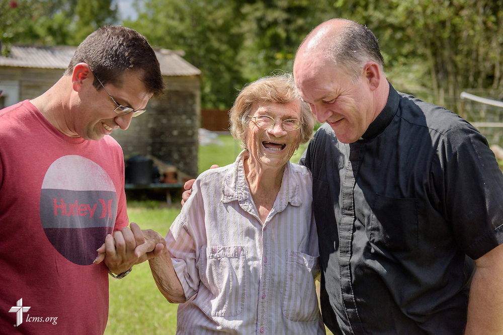 The Rev. David Buss, senior pastor of Trinity Lutheran Church, Baton Rouge, La., prays with charter member Althea Neptune and the Rev. Ross Johnson, director of LCMS Disaster Response, outside her flood-damaged home on Wednesday, Sept. 14, 2016, in Baton Rouge. LCMS Communications/Erik M. Lunsford