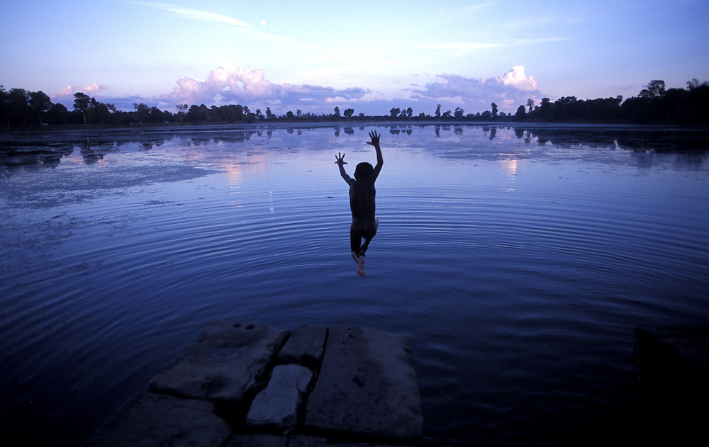 CAMBODIA - Angkor Wat.A young boy leaps into a baray (reservoir bordering the temples) to cool off