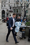 A City man carries a bunch of inflated balloons through Cornhill in the City of London, the capital's financial district, on 14th March 2018, in London England.
