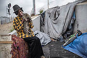Los Angeles, California, U.S. - <br /> <br /> Life On The Edge<br /> <br /> According to the Los Angeles Homeless Services Authority, the homeless population of Los Angeles and L.A. County has increased as much as 20% in the last year, and leads the nation in homeless unsheltered living, at nearly 70%.<br /> Homelessness here has grown substantially since the last El Niño, which dumped 30 inches of rain on Los Angeles during the winter of 1997-98, authorities say. Recently, the Los Angeles City Council declared a state of emergency on homelessness and called for $100 million to help address the growing crisis. The Los Angeles River flows through Los Angeles County, from Canoga Park in the western end of the San Fernando Valley, nearly 48 miles southeast to its mouth in Long Beach. Homeless people live along much of its length, with many located generally east of Downtown L.A., making their homes in and around the river, under overpasses or alongside rail lines and industrial wastelands. Those people - many dealing with disability, mental health and criminal justice issues - living in tents, improvised shelters and live-in vehicles, have increased 85% in the same period. Causes include high unemployment, low wages and escalating rents, coupled with gentrification and elimination of SRO hotels and cheap rooms, a last option for many. An estimated 800 people live in LA's riverbeds and storm drains, which will be deluged with powerful torrents when El Niño storms arrive in early 2016. Although the Sheriff's Department and LA's Homeless Services Authority have made numerous visits to warn residents, many see no compelling reason - or options - for moving. Most are not the transient homeless we are used to seeing but have set up semi-permanent living quarters in the LA River, which with its sweeping concrete vistas and city skyline sunsets may soon become both a beautiful and dangerous place to call home.<br /> <br /> LESHAWN holds her cat outside her home in a defunct tu