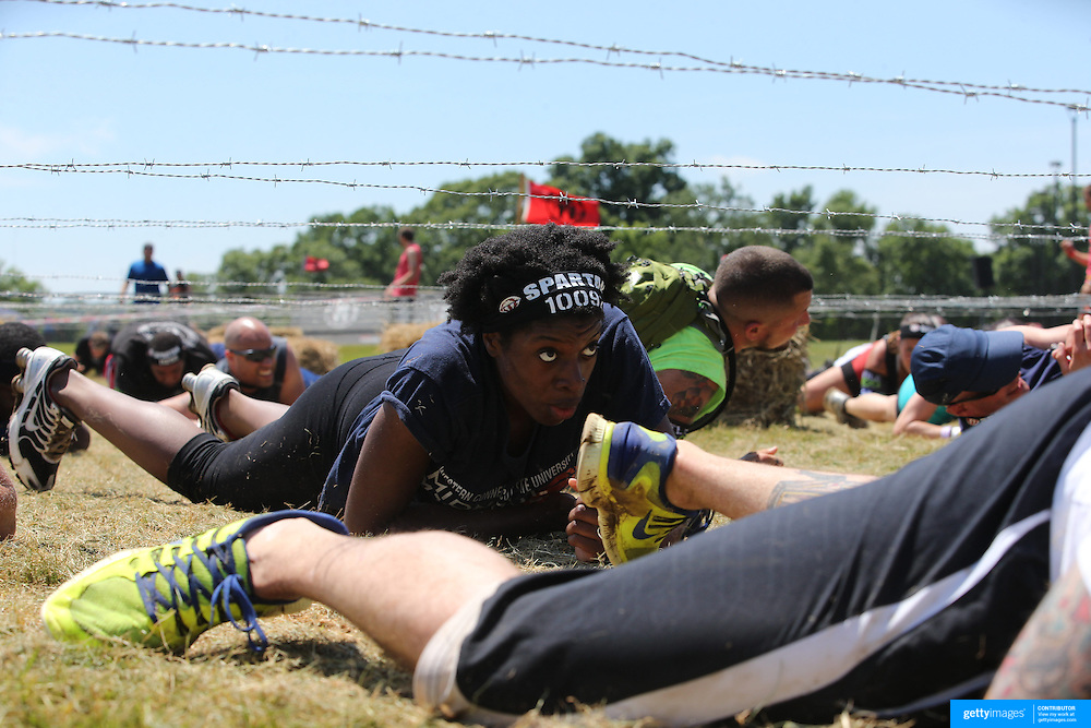 Competitors in action at the barbed wire crawl obstacle during the Reebok Spartan Race. Mohegan Sun, Uncasville, Connecticut, USA. 28th June 2014. Photo Tim Clayton