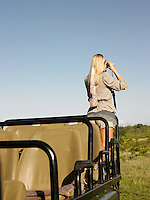 Young woman on safari standing in jeep looking through binoculars back view