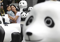 61633277<br /> A parent and her child pose for photos with lovely pandas during the 1St panda exhibition at Kerry Centre Square in Shanghai, East China, June 2, 2014. A total of 100 pandas made of leftover moso bamboos were displayed during the exhibition, Monday, 2nd June 2014. Picture by  imago / i-Images<br /> UK ONLY