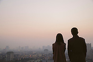 A young vietnamese couple contemplate a skyline cityscape at dusk in Hanoi, Vietnam, Southeast Asia