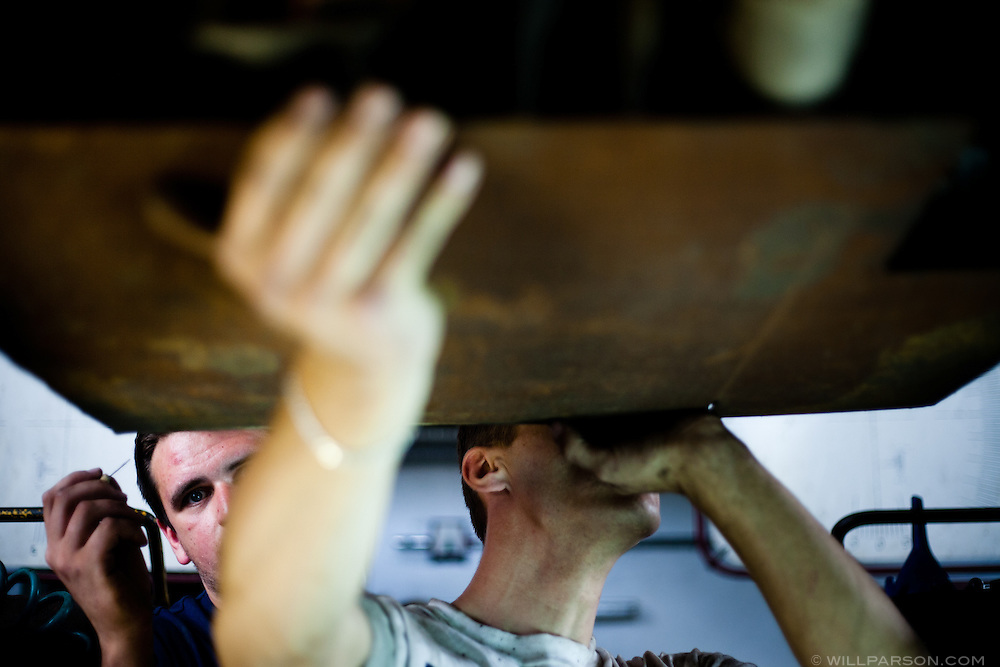 Russian mechanics attach a piece of scrap metal to the undercarriage of our Nissan Micra in Lodz, Poland. The metal would protect the car from scrapes and punctures on the mostly unpaved roads of Mongolia.