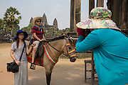 A young Asian boy sits on a horse and poses for his mother taking a photo with his sister standing by his side in the background is Angkor Wat Siem Reap, Cambodia. Angkor Wat is a temple complex in Cambodia and the largest religious monument in the world, with the site measuring 162.6 hectares. It is Cambodia's main tourist destination.  (photo by Andrew Aitchison / In pictures via Getty Images)