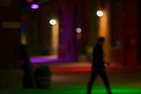 Man walking at night in the Distillery District, Toronto.