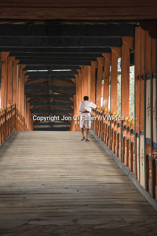 A Bhutanese man in the traditional gho robe crosses the covered bridge of the Punakha Dzong, Punakha, Bhutan.